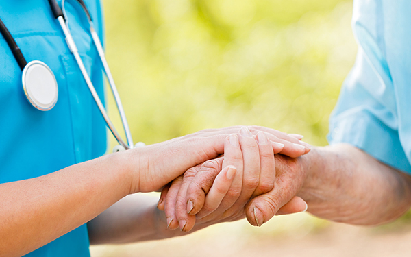 Doctor or nurse holding elderly lady's hands.